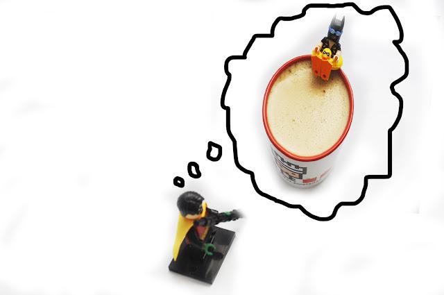 Robin de lego, tiene una nube de pensamiento donde se ve una imagen de una taza de vidas pixeladas con café y un batman con flotador apunto de meterse en la taza