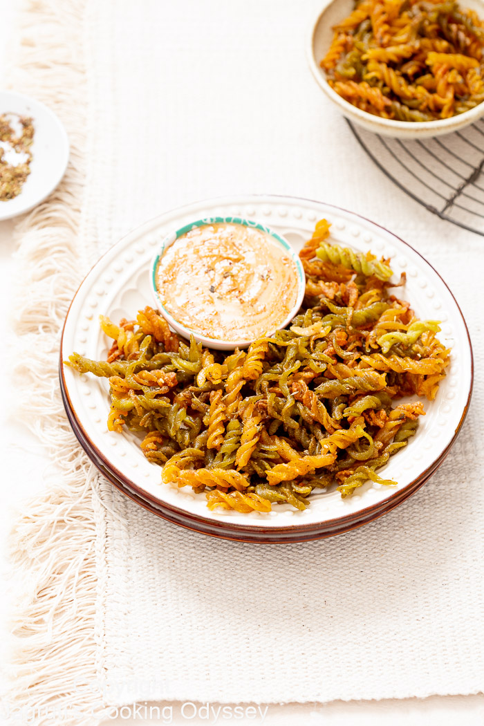Vegan, low carb and gluten free lentils pasta chips served with tahini and harissa sauce on a mat