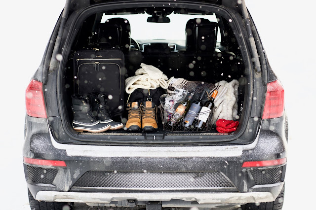 Mercedes Benz truck with the trunk open carrying Tumi luggage and wine