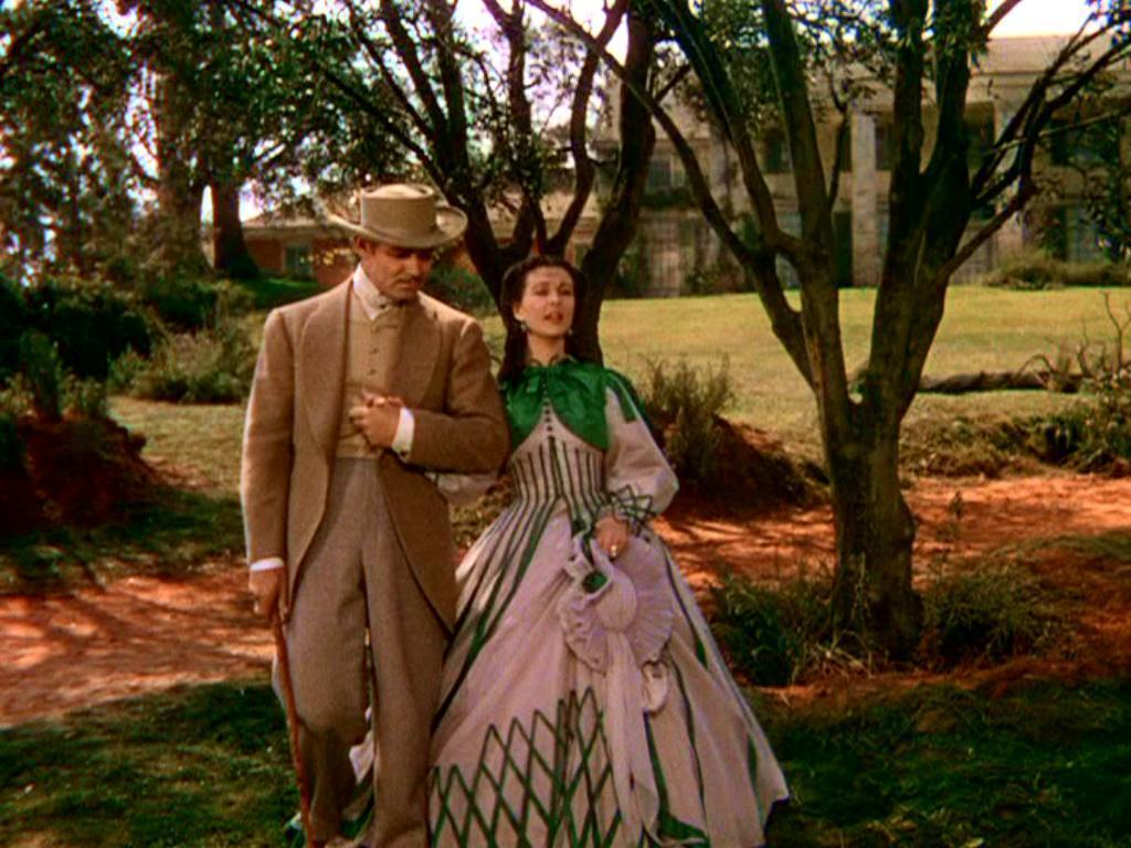 Clark Gable as Rhett Butler and Vivien Leigh as Scarlet O'Hara walking outside Tara in Gone with the Wind movieloversreviews.filminspector.com
