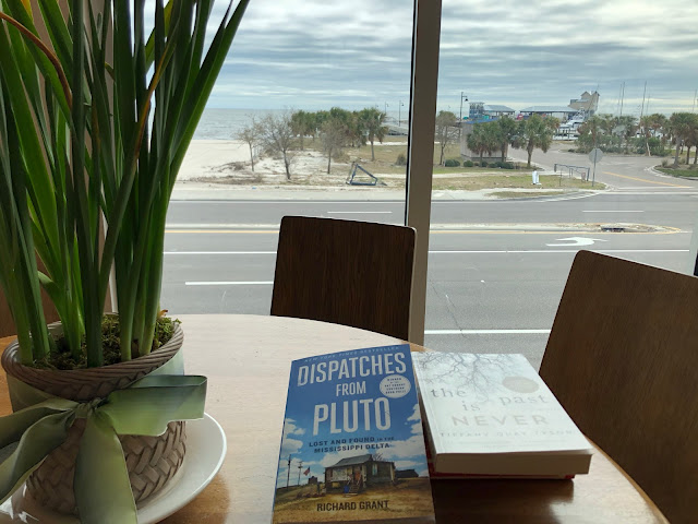 books on a table with view of beach