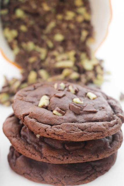 stack of peppermint stuffed chocolate cookies with mint chocolate baking chips in background