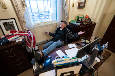 Richard Barnett kicks up his feet at Nancy Pelosi's desk, leans back, and holds his smartphone.