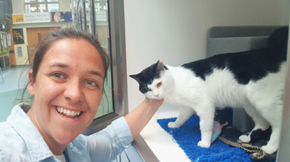 brunette woman stroking black-and-white cat in Cats Protection pen