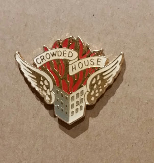 "An enamel pin on gold metal. A stylised white 3 storey building, framed by white and gold angel wings, has red and gold flames leaping from the top. Above the flames is a white scroll with gold lettering saying ""CROWDED HOUSE"""