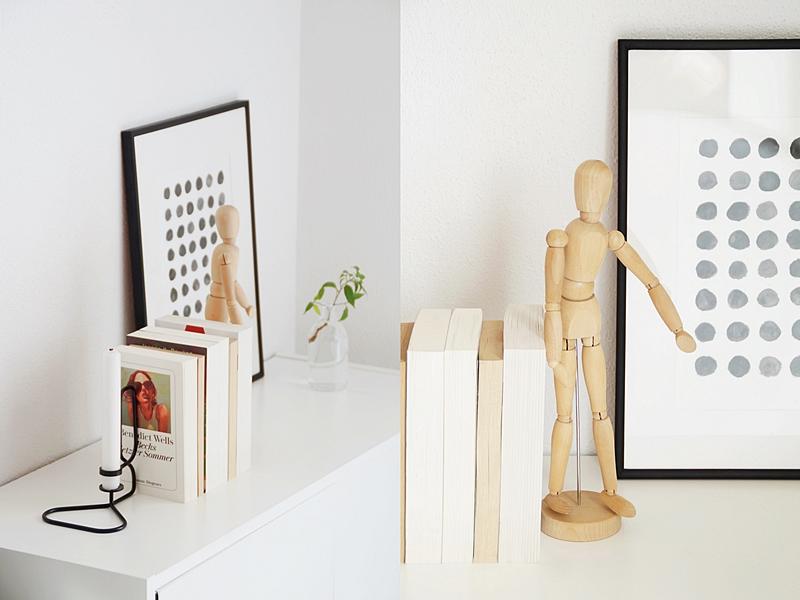 Kommode skandinavisch modern reduziert dekorieren in Schwarz, Weiß, Naturtönen und mit einem grünen Zweig für Leben