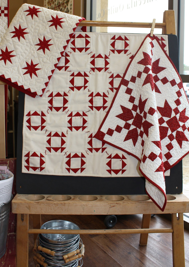 red and white quilt designs with stars, snowflakes and squares and triangles displayed on shop