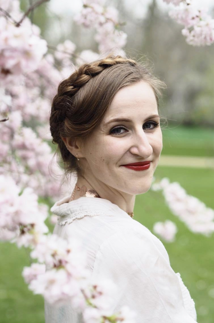 woman with milkmaid braids surrounded by blossom trees