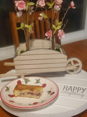 small piece of cake on a decorative plate, sitting on a table with spring flowers