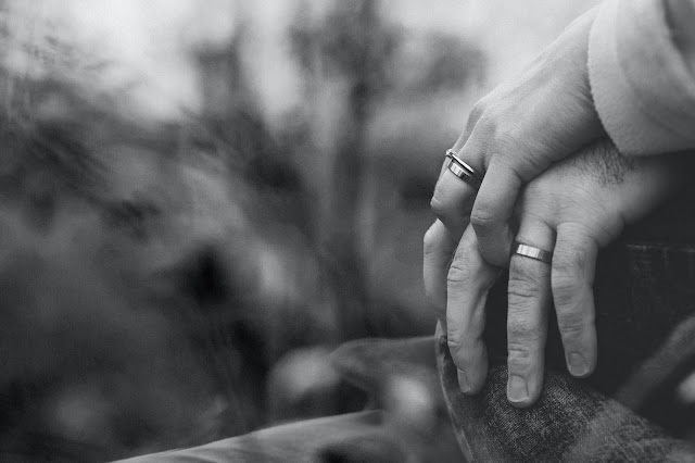Black and white image on 2 hands on top of each other wearing wedding rings