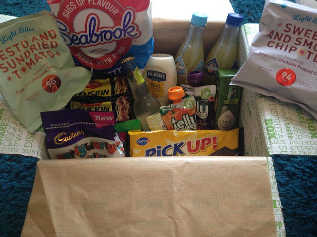 A degusta subscription box containing a selection of snack foods and drinks