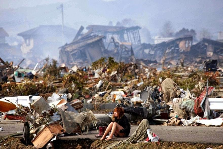 30 of the most powerful images ever - A woman sits amidst the wreckage caused by a massive earthquake and ensuing tsunami, in Natori, northern Japan, in March 2011