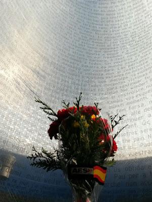 Un ramo de flores con el monumento a las víctimas del 11M de fondo