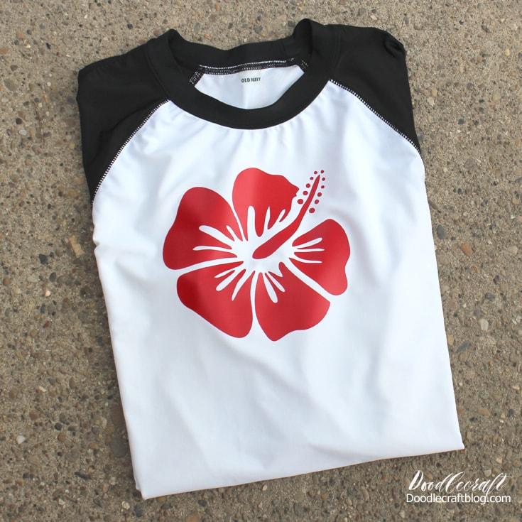 White rashguard with black sleeves decorated with red sportflex iron on vinyl with tropical hibiscus flower.