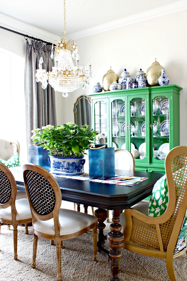 green china cabinet, kate spade leokat fabric, blue glass lanterns, dining room centerpiece, hydrangeas, kate spade brush strokes table runner, blue and white, vintage crystal chandelier, blue willow, black and white houndstooth drapes, vintage cane wingback chairs