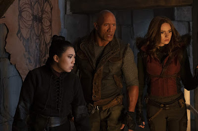 "Ming Fleetfoot (Awkwafina), Dr. Smolder Bravestone (Dwayne Johnson), and Ruby Roundhouse (Karen Gillan) must make their way through sand and ice to defeat Jurgen the Brutal (Rory McCann) in the movie ""Jumanji: The Next Level"" (2019)."