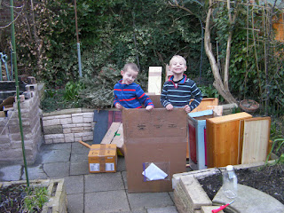 fuel for bonfire and 2 boys standing in a cardboard box