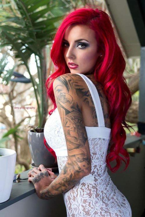 Espectacular mujer de pelo rojo tatuada, esta en un balcon y se gira para mirarnos, lleva tatuajes estilo chicano