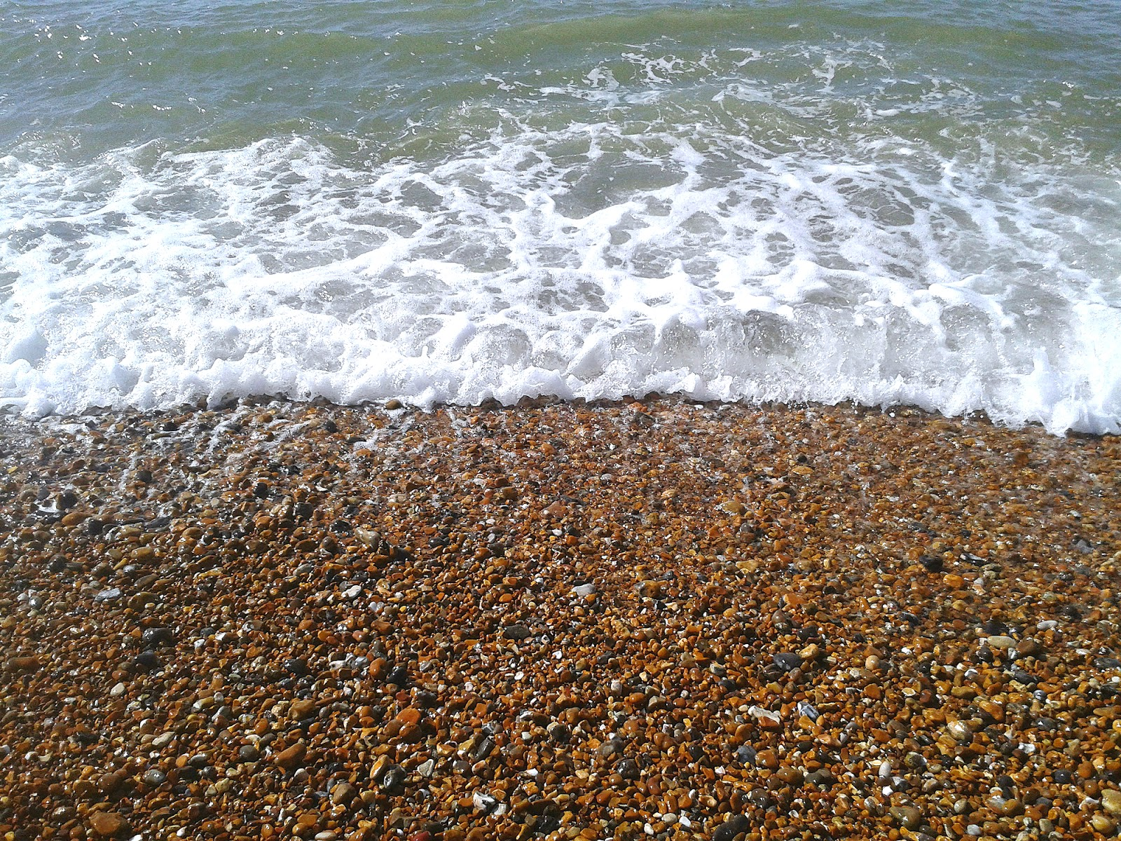 A shot of the waves coming in and covering the pebbles on the beach