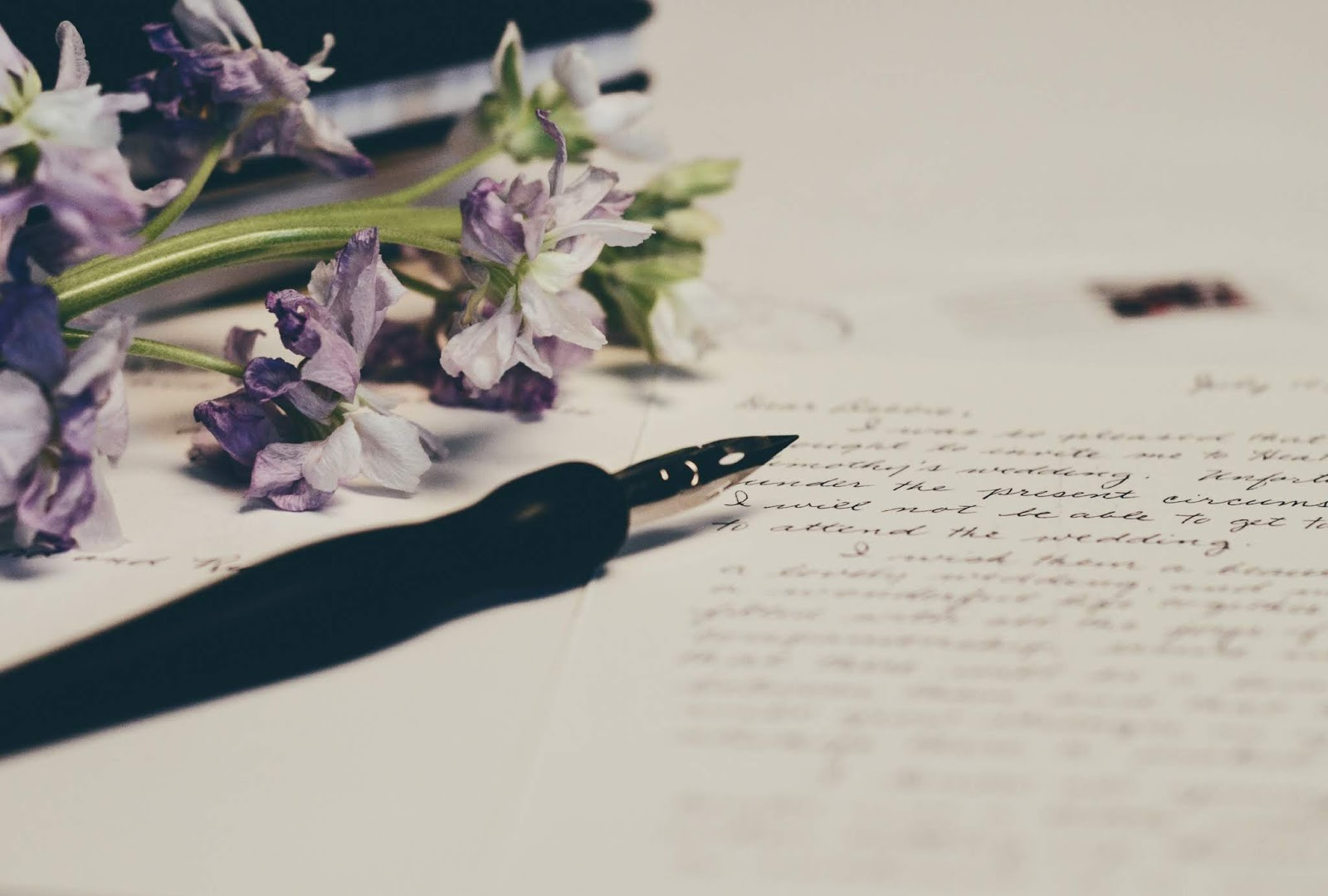 A photo featuring a black fountain pen bottom left, at an angle, with the nib in the centre partly on top of a mostly out of focus handwritten letter that's bottom right, with an out of focus envelope top right, slightly under the letter, and some lilac flowers to top left