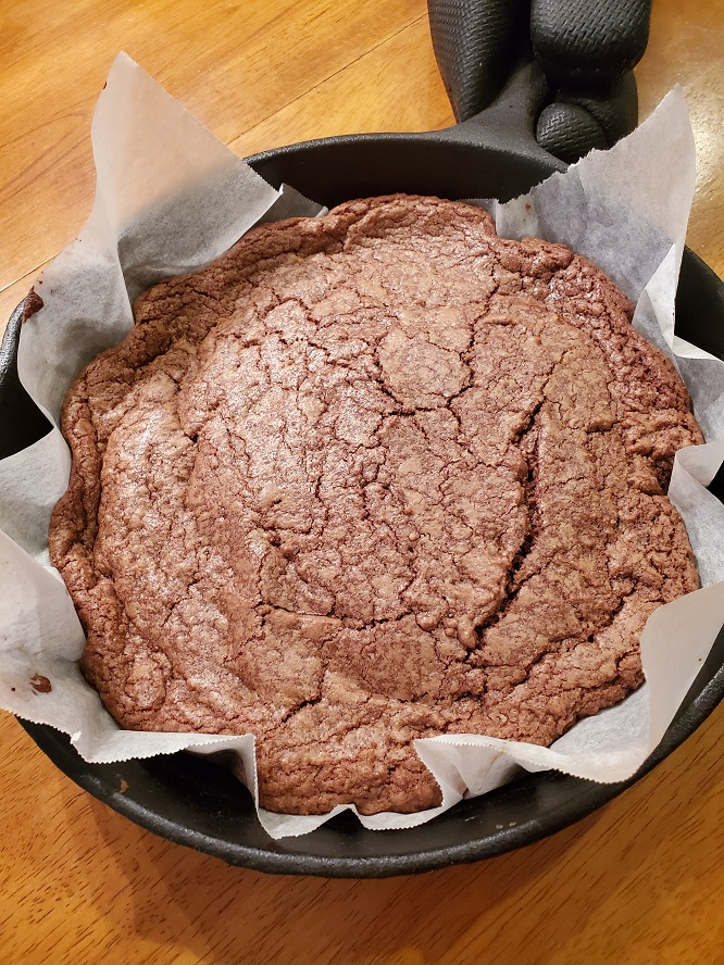 This is a baked chocolate skillet cookie. This is a cookie baked and is cooling in a 10 inch cast iron skillet lined with parchment paper and resting on a oak table and there is a black potholder on the handle