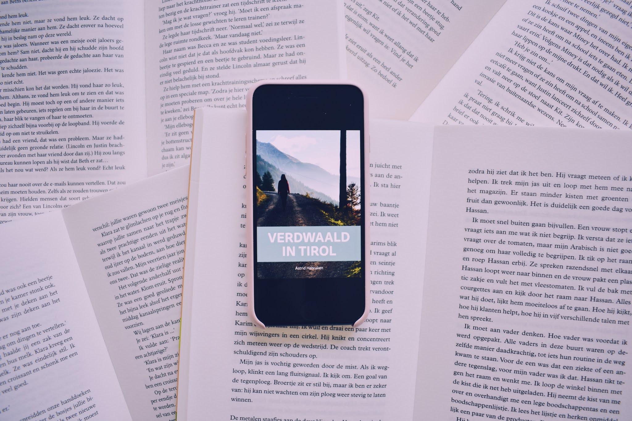 Cover van Verdwaald in Tirol op een met opengeslagen boeken gevulde achtergrond.