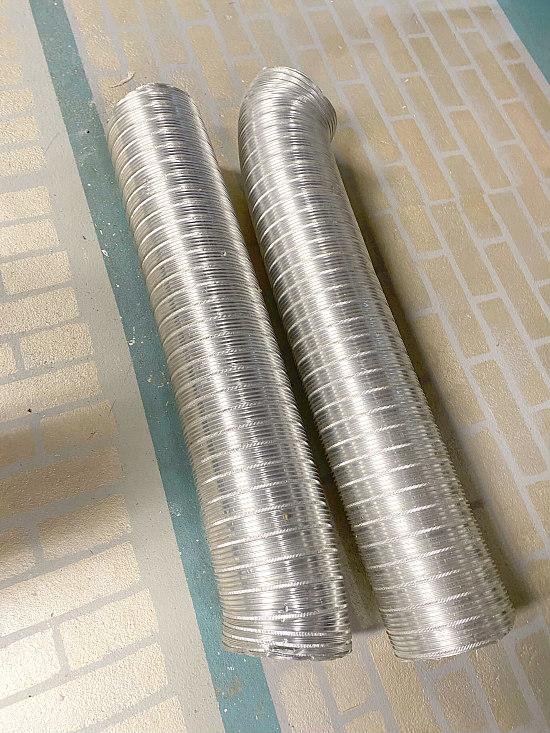 2 pieces of ductwork on golden brick floor