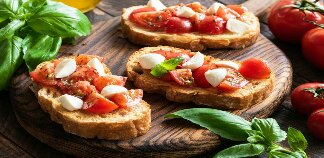 Bruschetta is an starter dish from ------ consisting of grilled bread rubbed with garlic