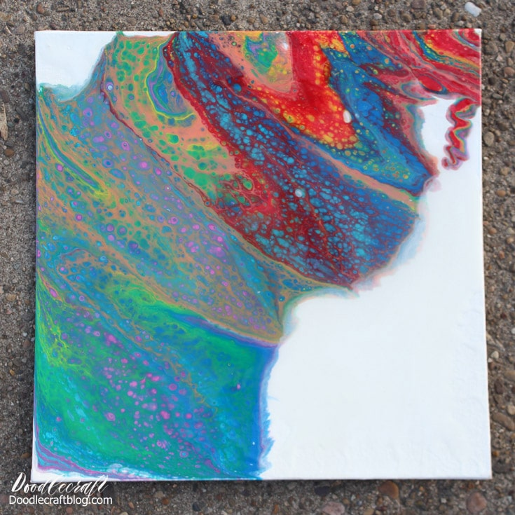 Rainbow colors dirty pouring acrylic paint on canvas for a stunning piece of art.