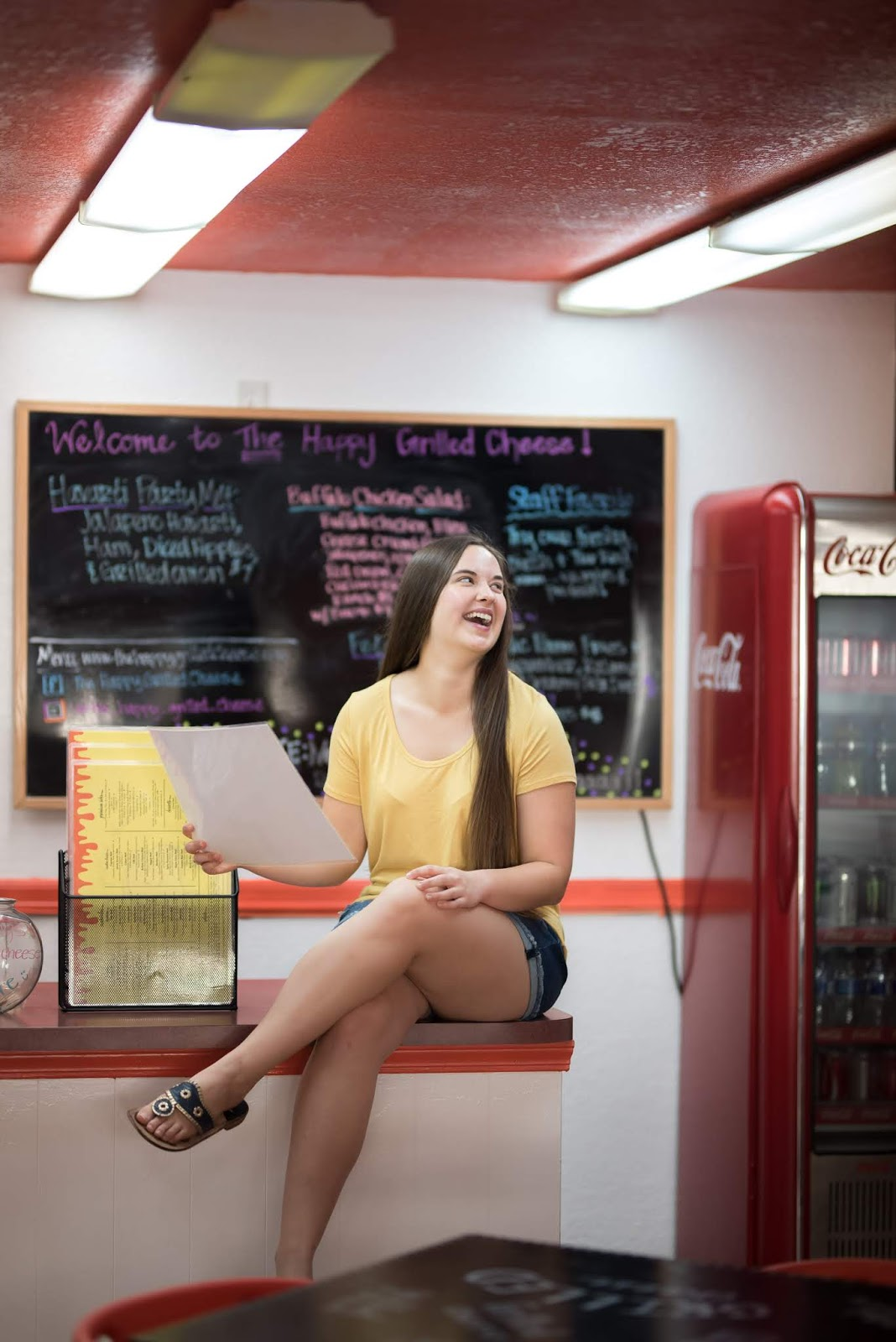 Brunette girl holding menu at The Happy Grilled Cheese restaurant in downtown Jacksonville Florida