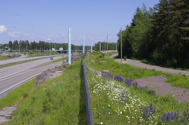 kuvassa tieliittymä sivusta kuvattuna kesäaikaa. Keskellä kuvaa turkoosinvärisiä pylväitä tienreunalla.Etualalla kukkaniittyä.