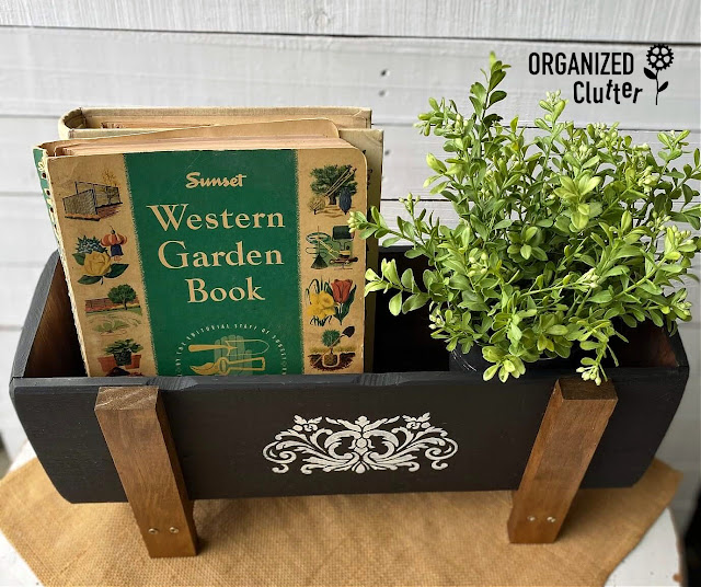 Photo of newly painted & stenciled flower box with a faux plant & vintage garden books