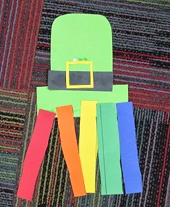 Leprechaun art for toddlers using construction paper to make a green leprechaun hat with a black belt, gold buckle on it, and rainbow streamers hanging off of it.
