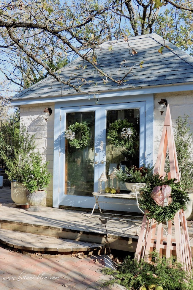 Existing evergreen shrubs in French Country style urns are supplemented with fresh greenery to add Christmas cheer to the garden house