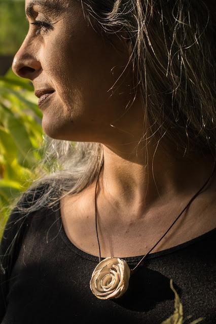 Mulher com semblante sereno usando colar de cerâmica em formato de rosa