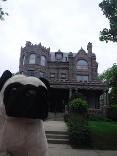 a plush pug appears in front of a mansion built in reddish stone in the Richardsonian Romanesque style