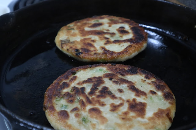 green onion cakes cooking on a cast iron pan