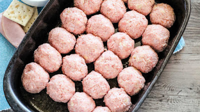 raw ham balls formed and placed in pan, ready to bake