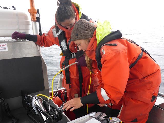 Kaksi henkeä pelastautumispuvuissa veneen kannella ihmettelee vedenalaista videokameraa