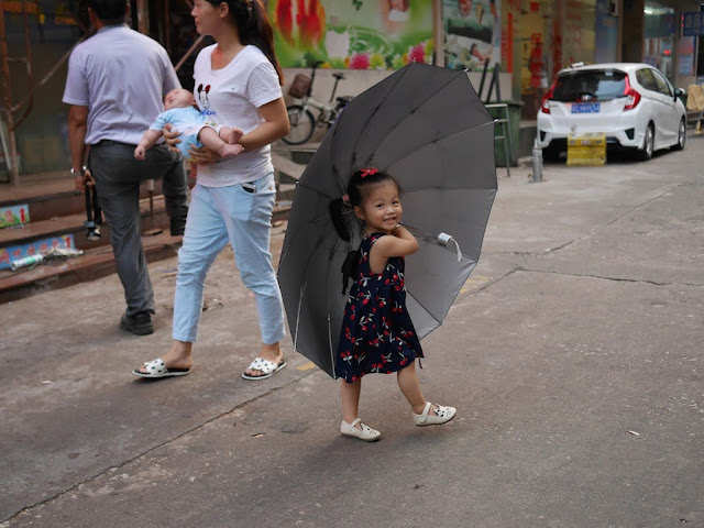 little girl smiling and holding a large umbrella in Zhuhai, China
