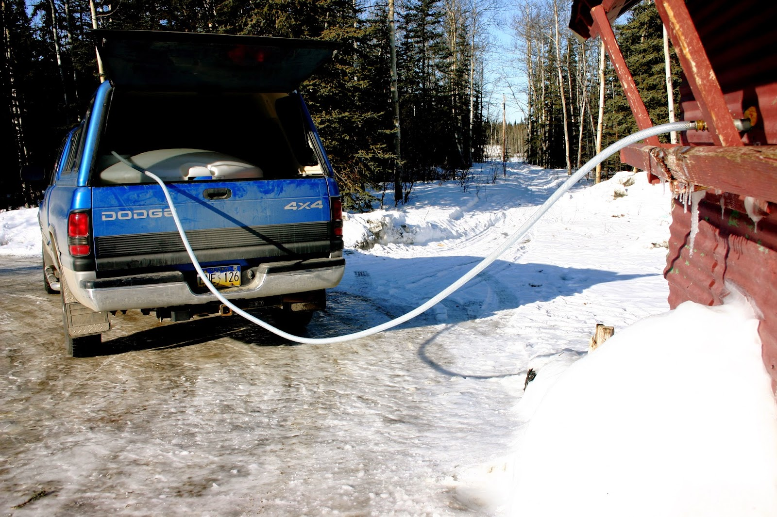 Winter water hauling with a pickup and tank in rural Alaska