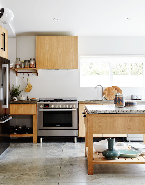 flat light wood kitchen cabinets, center island with shelf underneath for serveware, stainless steel Bosch gas oven with feet, milk glass globe light, open shelves with mason jars and Japanese whisk broom