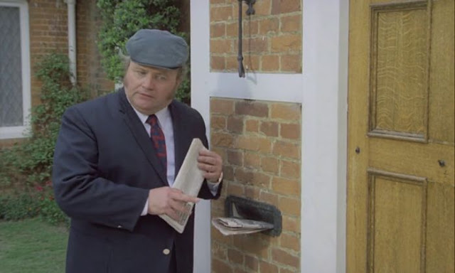 Harry Secombe standing outside the front door of a house