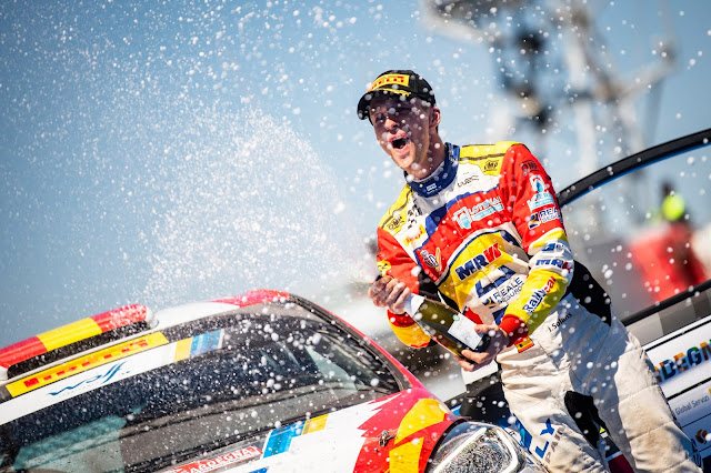 Jan Solans celebrates spraying champagne after winning Junior World Rally Championship