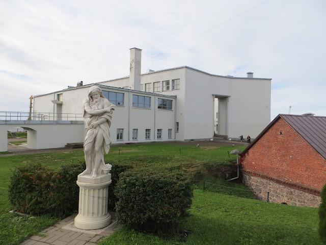 Etualalla valkoinen kivinen miespatsas ja taka-alalla valkoinen taidekoulu- ja museorakennus. Värivalokuva.