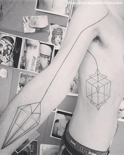 Um par de elaborar formas geométricas são conectados por uma linha preta que atravessa o portador do tronco e braço esta tatuagem.