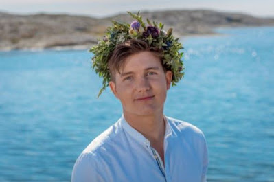 Porträttbild av Daniel Norberg framför havet, med midsommarkrans på huvudet.