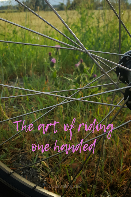 Bike tire and spokes with weeds and grass text reads The Art of riding one handed. www.ruralmag.com