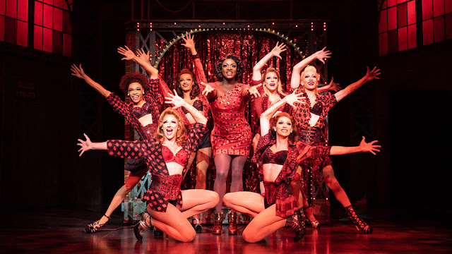 An actor of colour wears a sparkling red dress and heels, surrounded by drag queens in red and black skimpy costumes
