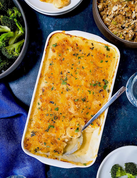 Top view of potato cheese casserole in a white casserole dish on a blue background.